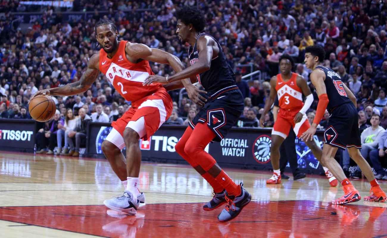 Kawhi Leonard #2 of Toronto Raptors dribbles ball as Justin Holiday #7 of Chicago Bulls defends during NBA game on December 30, 2018 in Toronto