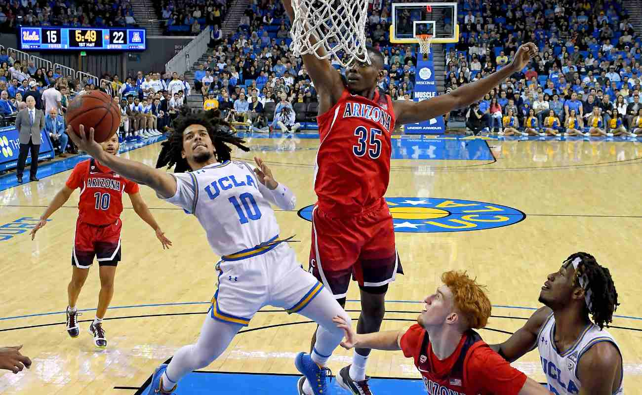 Tyger Campbell #10 of the UCLA Bruins gets by Christian Koloko #35 of the Arizona Wildcats for a basket in the game
