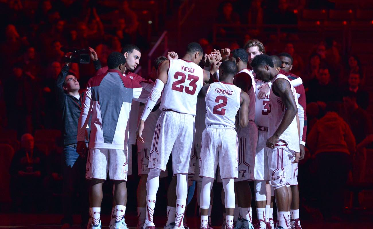 The Temple University basketball team huddle as the arena is still lit in red