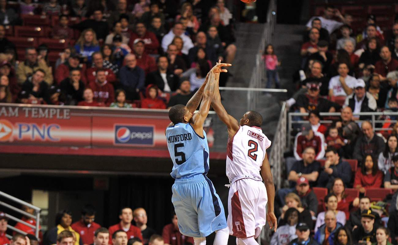 Temple University contests a jumper by URI during basketball game