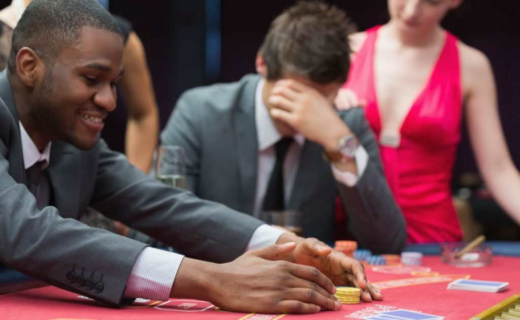 Man wins the pot at a casino as another man is comforted by a woman for losing