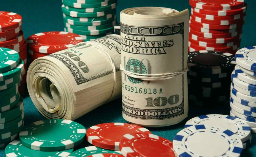 Rolled banknotes and casino chips on top of the table