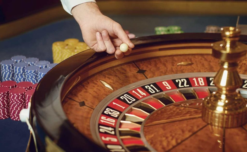 Croupier puts a roulette ball on the wheel at a casino