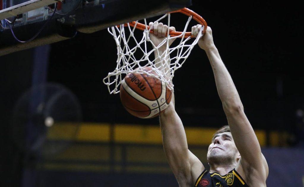 Ivan Basualdo of Obras dunks basketball in a game vs Olimpico.