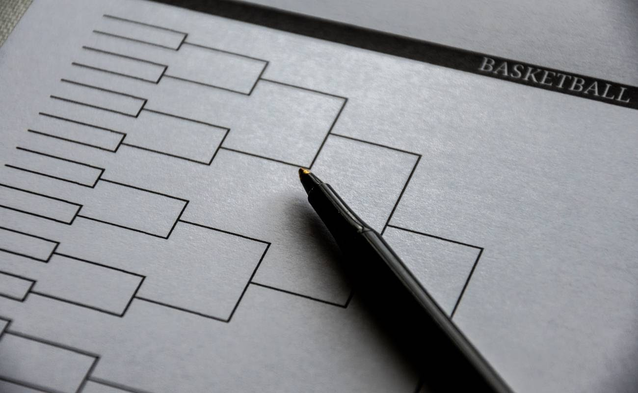 Blank basketball grid on paper and pen on top.