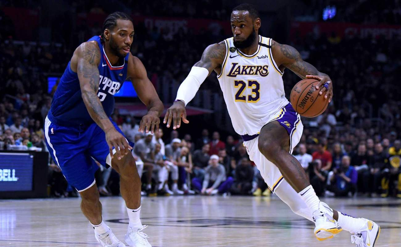 LeBron James #23 of the Los Angeles Lakers drives to basket past Kawhi Leonard #2 of LA Clippers