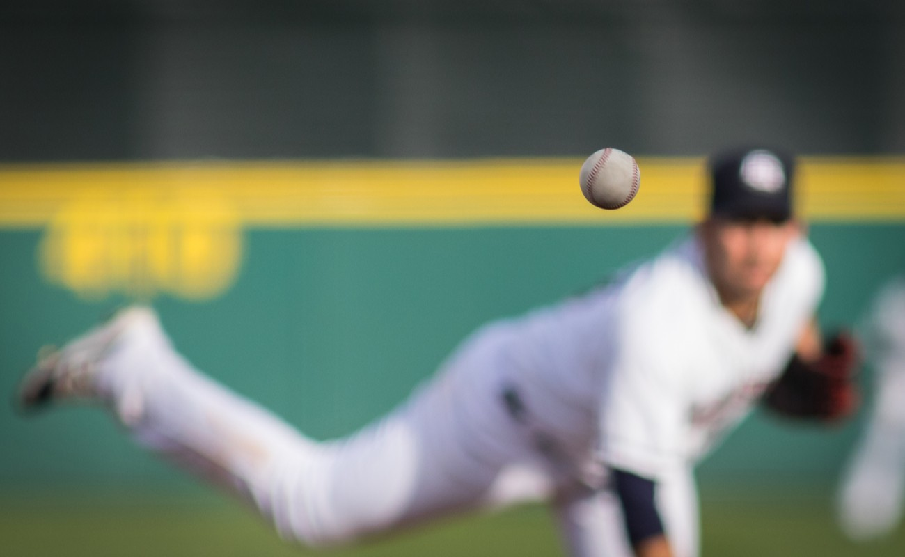 A baseball in motion with pitcher in background.