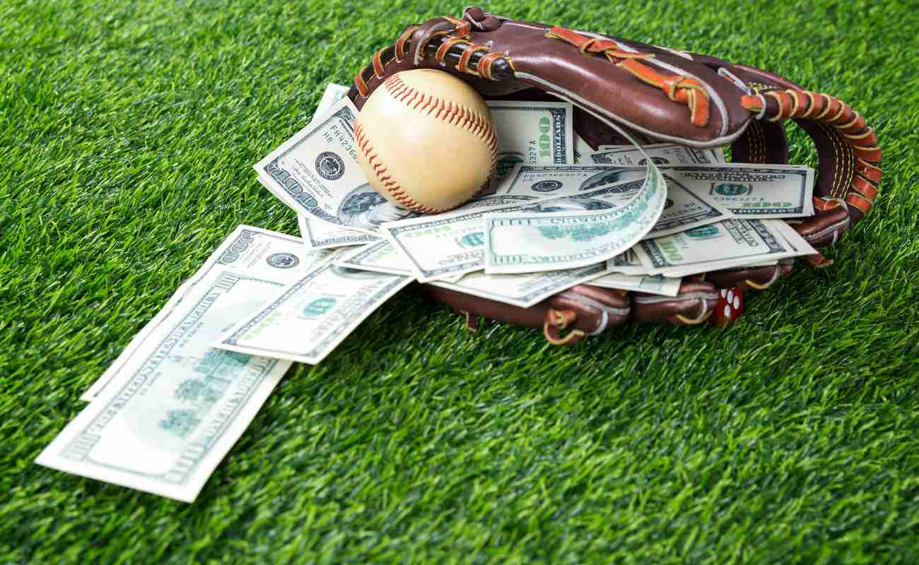 baseball in a glove with dollar bills in concept of getting money with bets in baseball