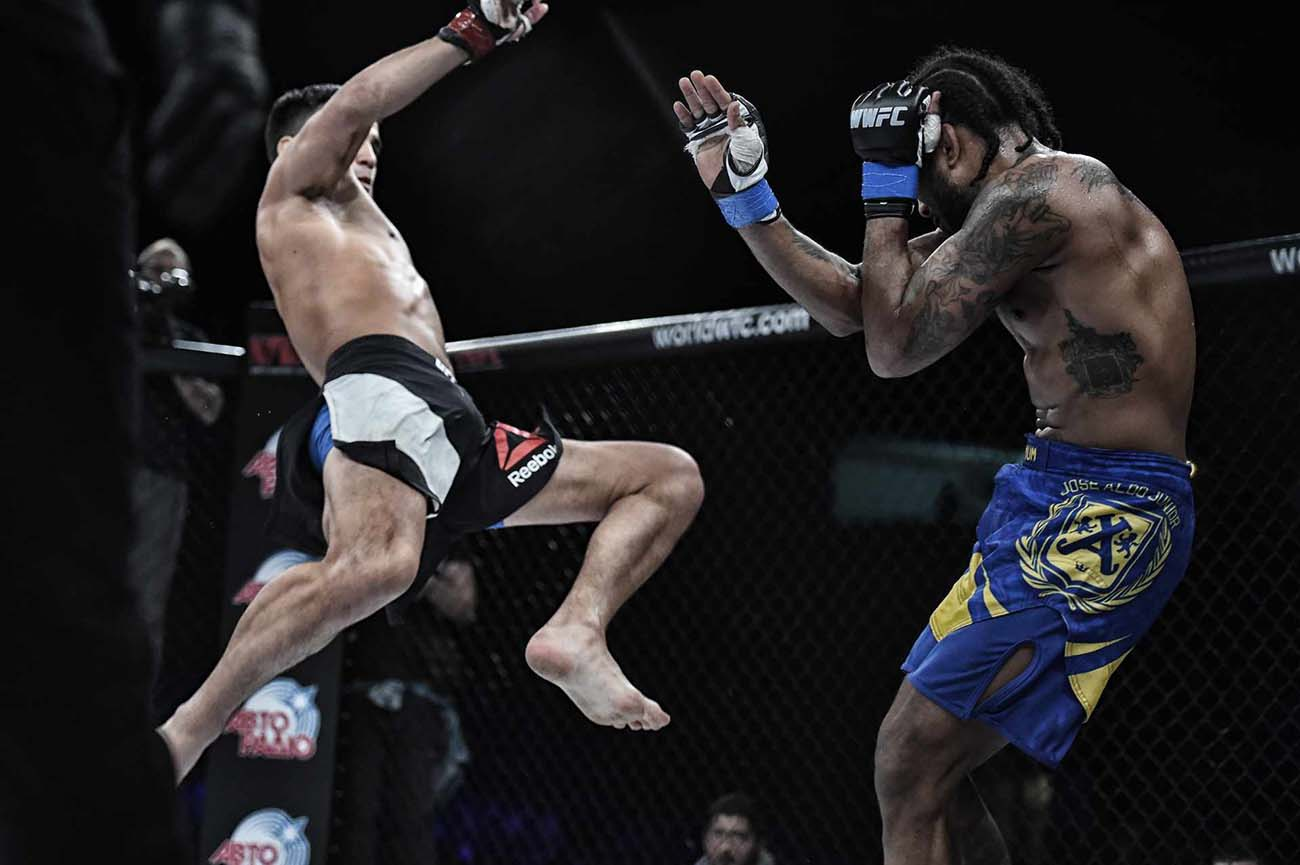 mma fighter delivering a huge flying kick to his opponent