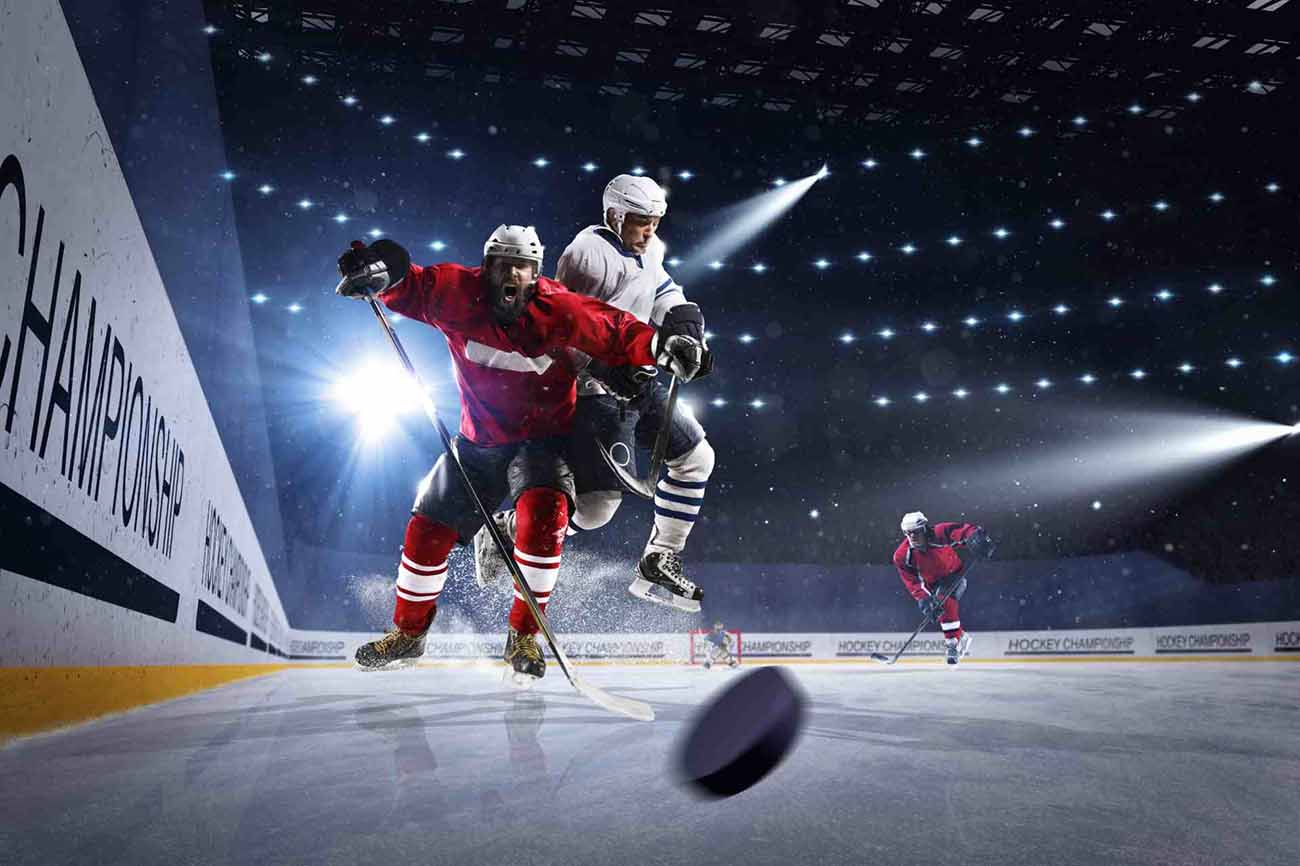 two ice hockey players charging aggressively for the puck