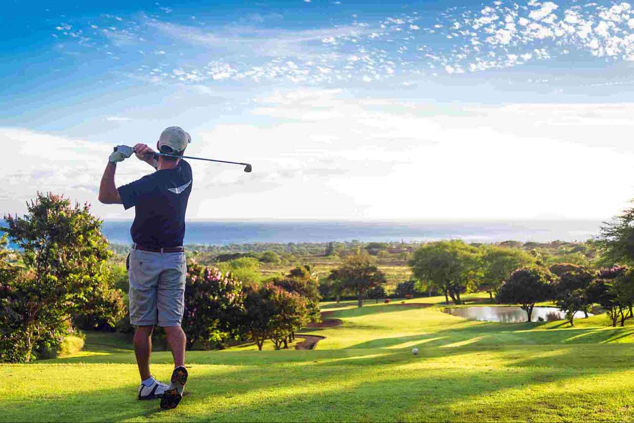 golfer teeing off on a beautiful hole with a view of the ocean in the distance