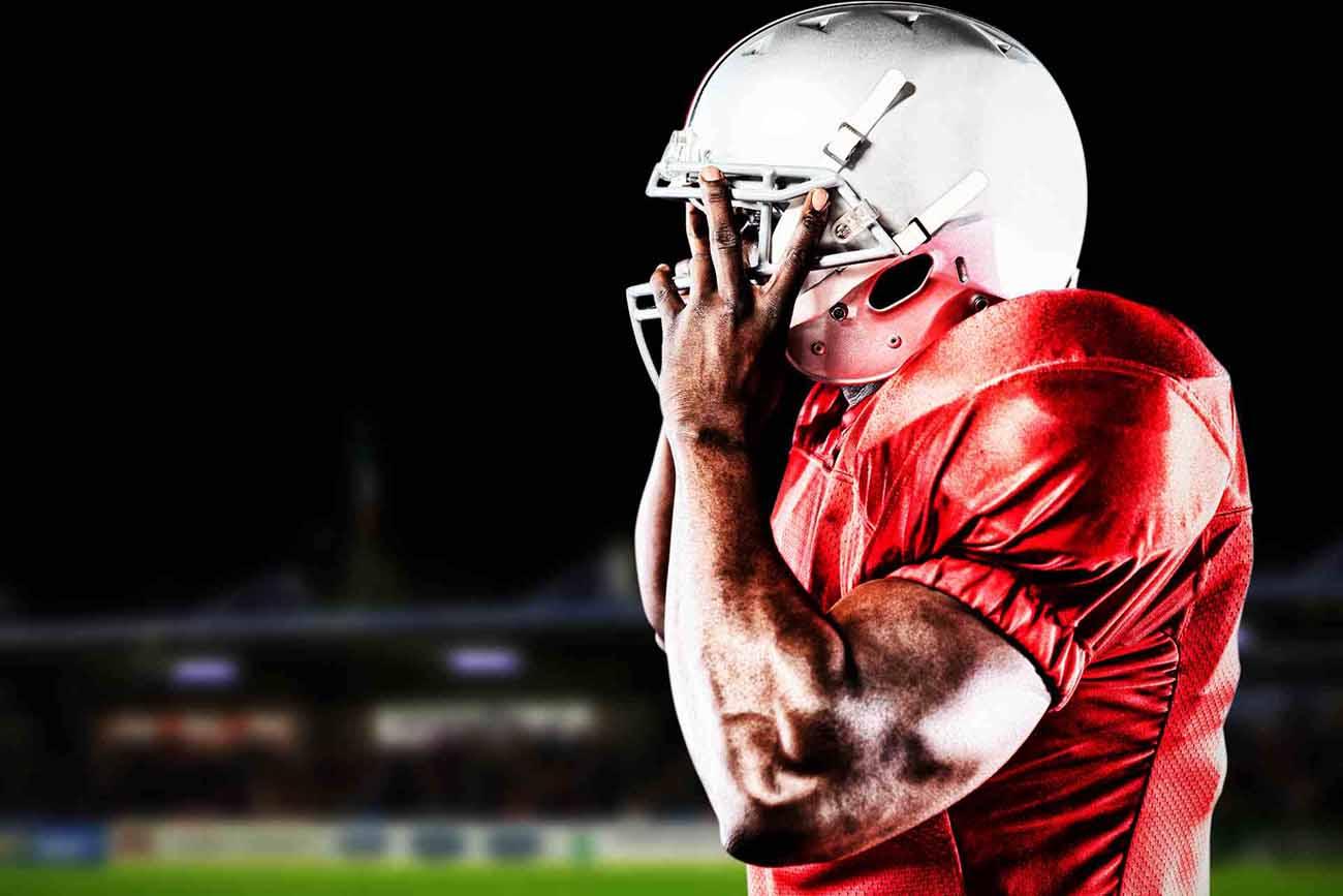 american football player positioning his helmet