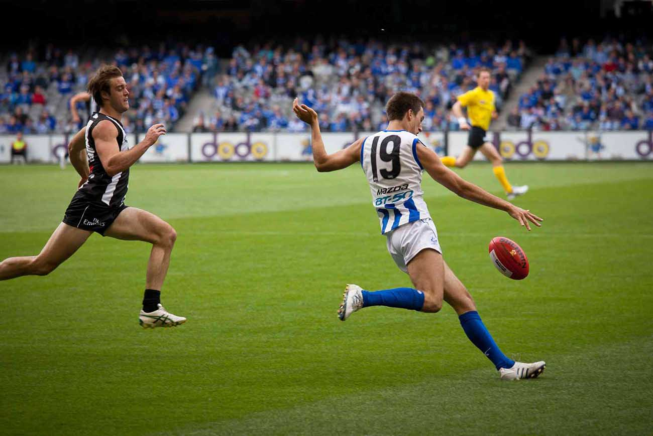 Australian football player getting ready to punt the ball