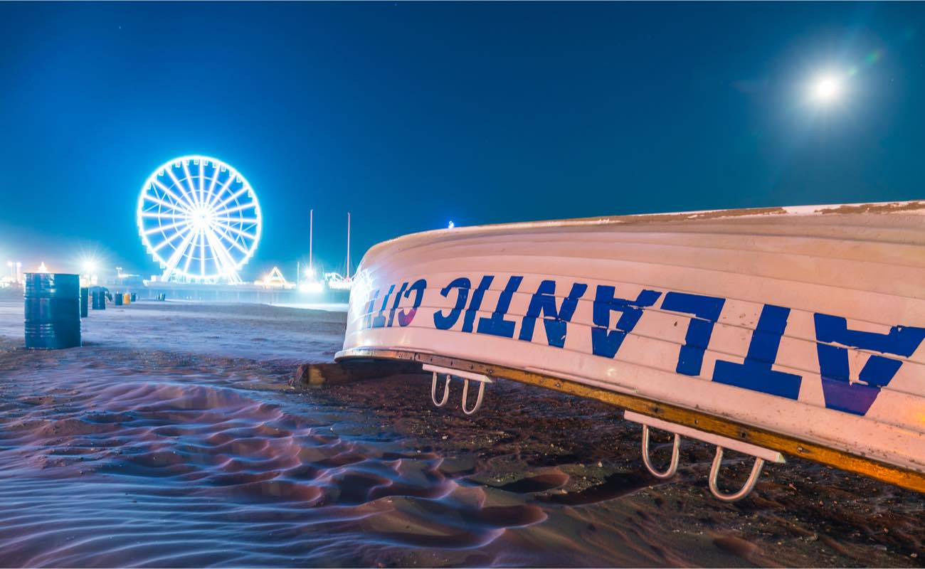 Atlantic City Boardwalk at night with overturned boat in foreground