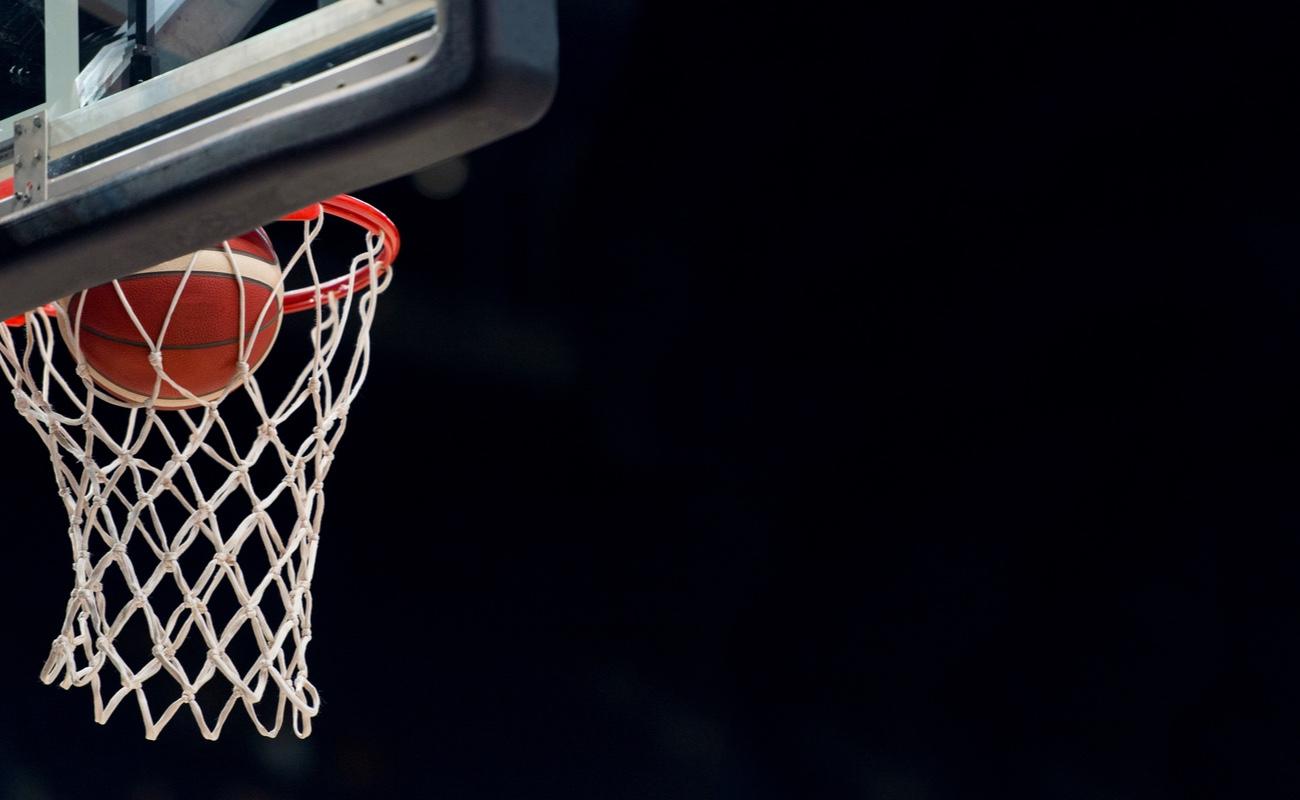 basketball in hoop against black background