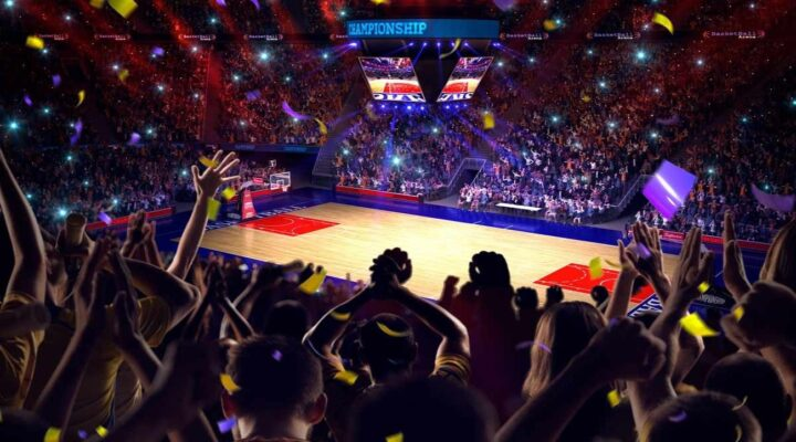 View of a basketball stadium from the crowd, with fans cheering and throwing confetti