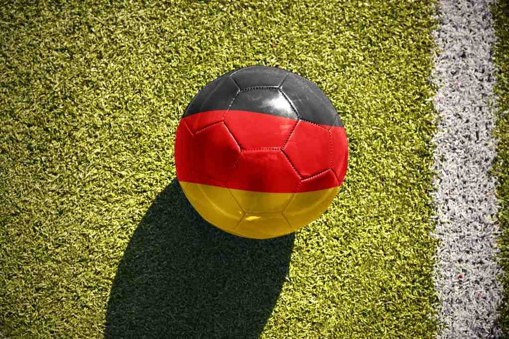 Soccer ball with German flag colors on a grass soccer field