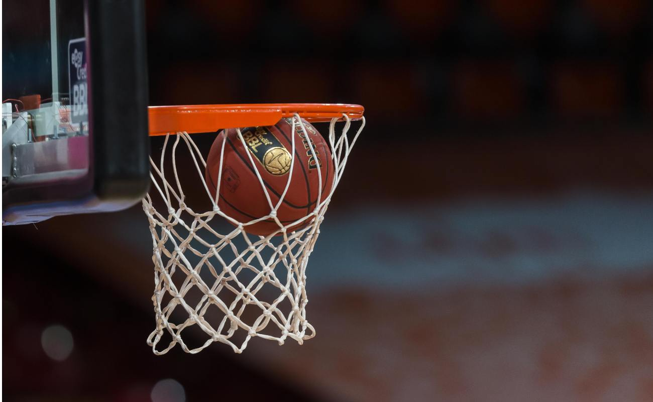 A basketball going through the hoop into the side netting