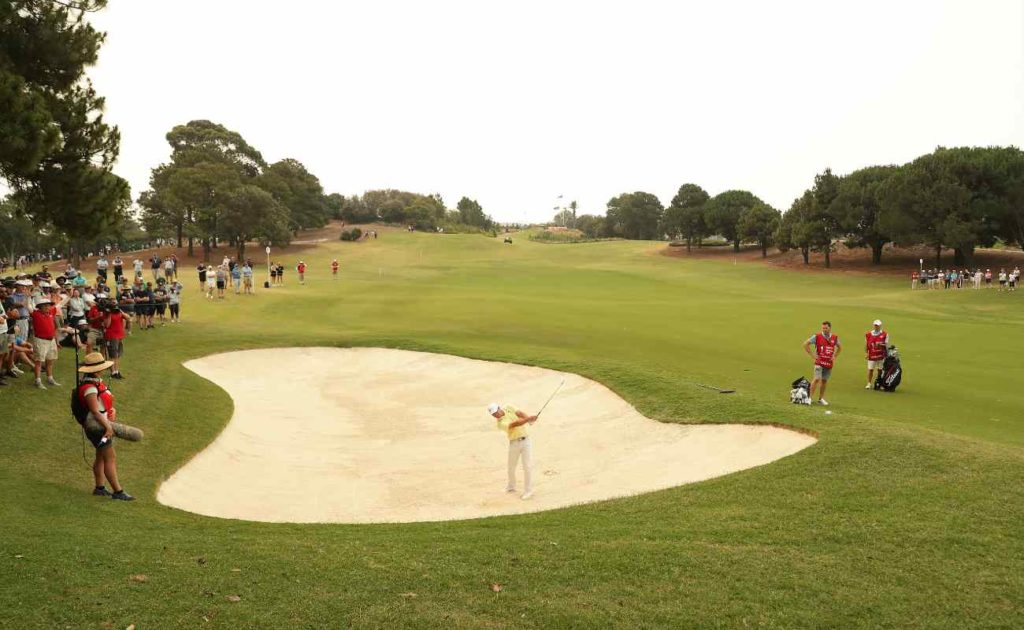 Fans watch golf player Paul Casey of England play out of a bunker at the 2019 Australian Open.