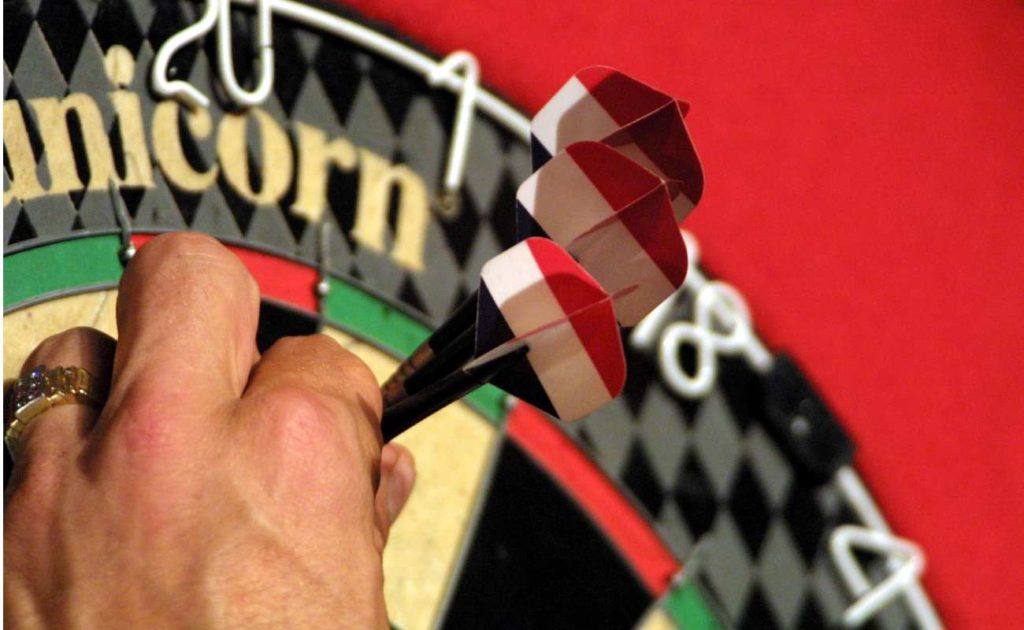 A hand taking darts out of a dart board