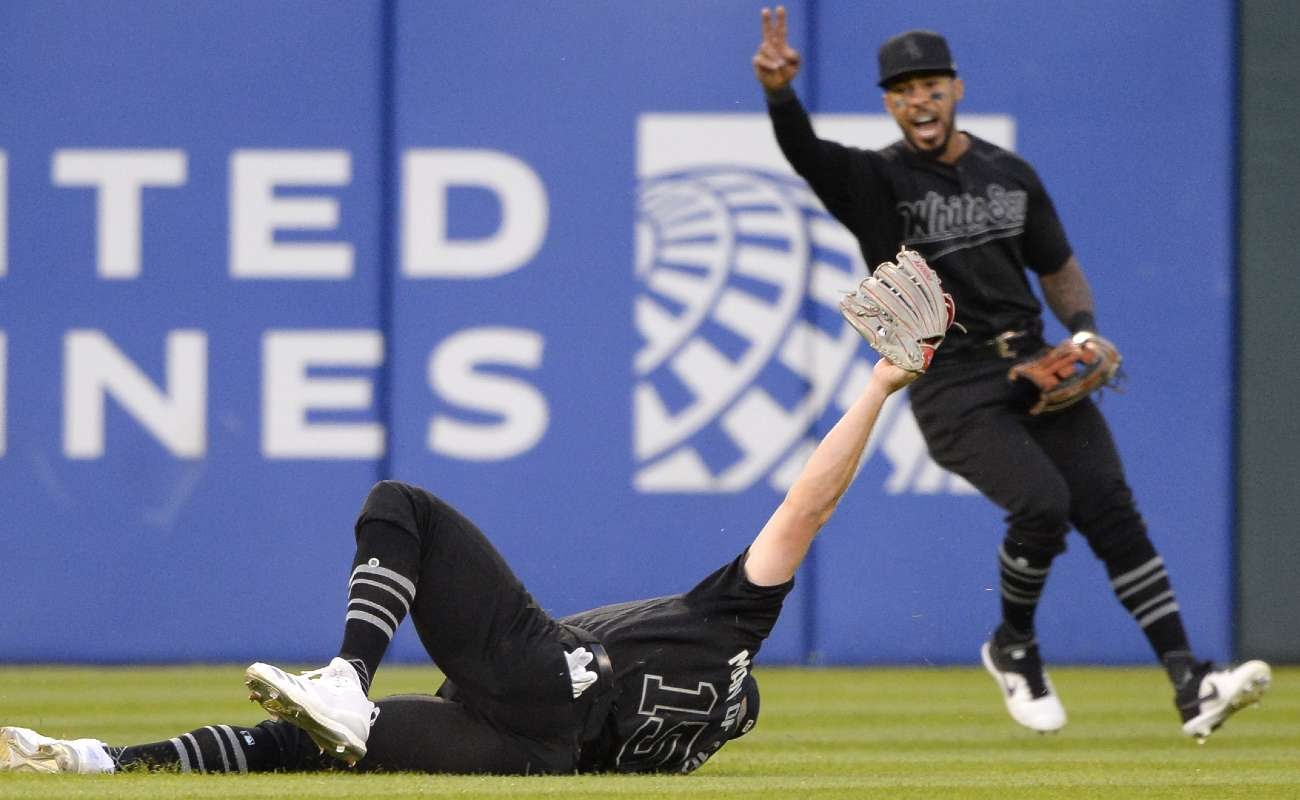Baseball player Adam Engel of the Chicago White Sox makes a diving catch against the Texas Rangers and his teammate celebrates in the background.