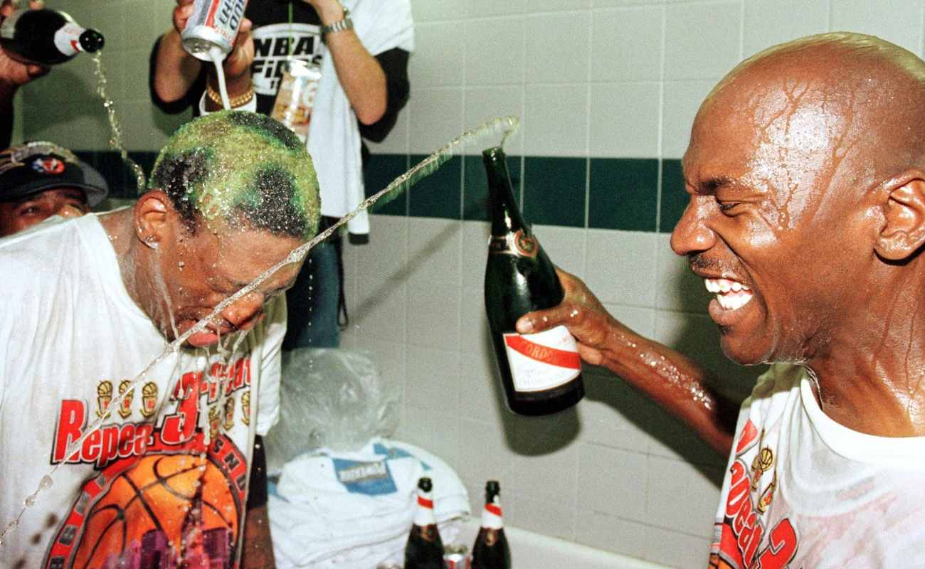 Dennis Rodman of Chicago Bulls gets beer and champagne poured on head by teammate Michael Jordan after winning NBA Finals
