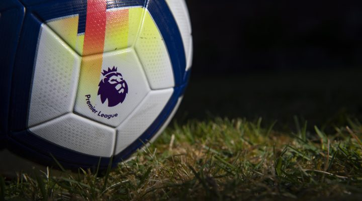 The Premier League logo printed on a match ball against a dark field background.