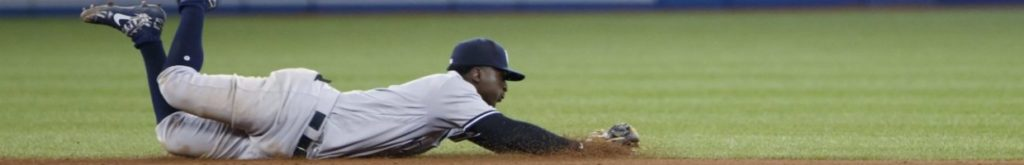 Baseball player Didi Gregorius of the New York Yankees dives for a ground ball off the bat of Bo Bichette of the Toronto Blue Jays