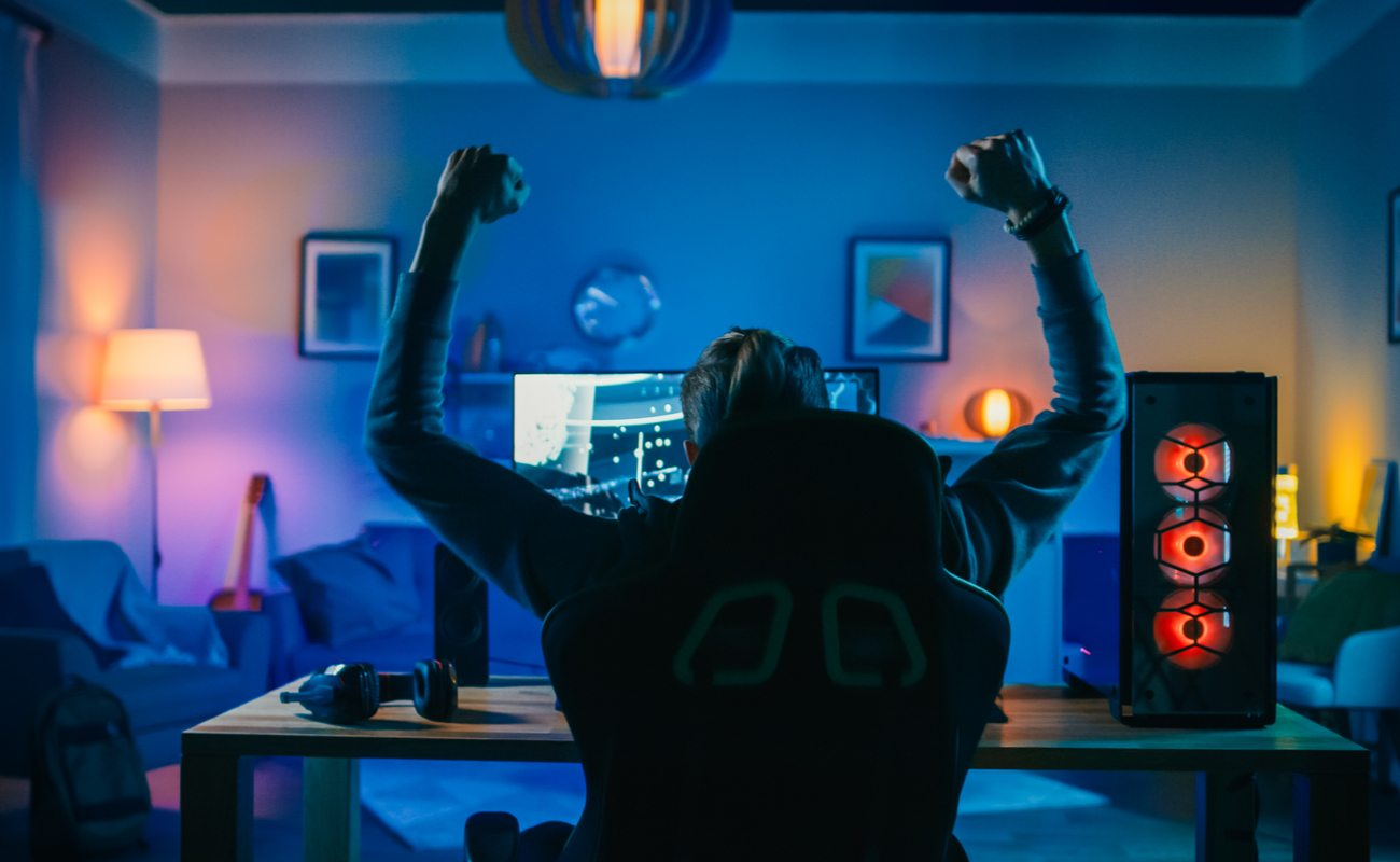 Gamer with arms in the air sitting in front of a desktop
