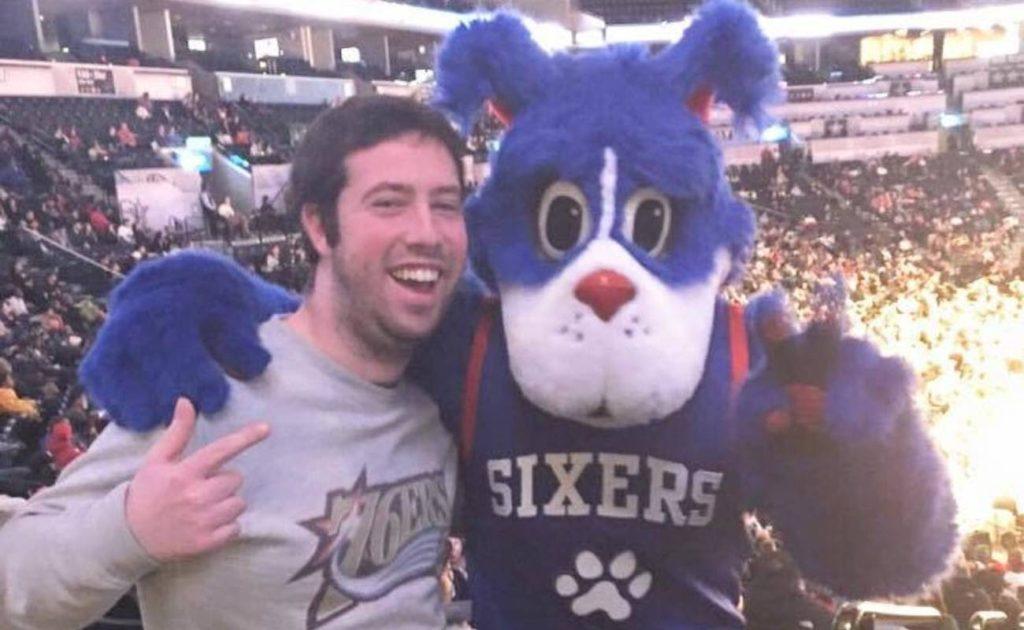 Fan posing with Philadelphia 76ers team mascot Franklin The Dog