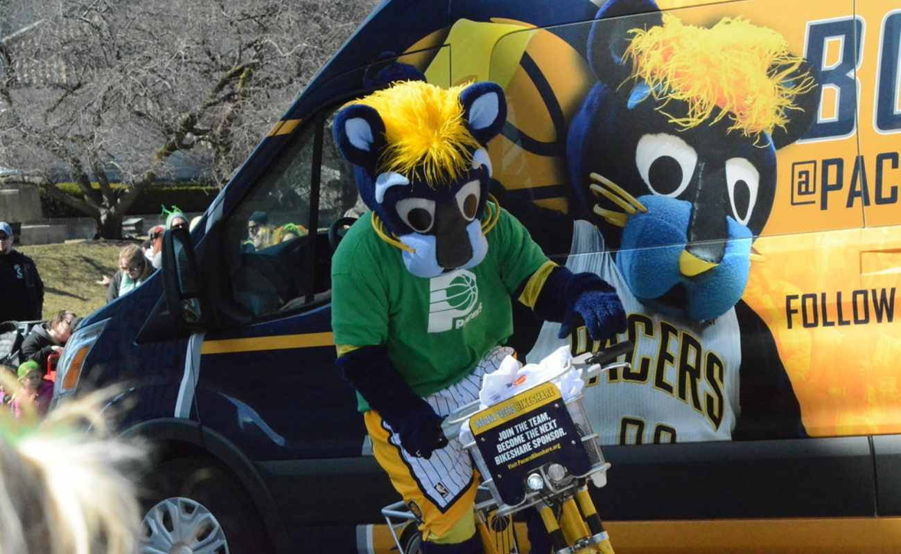 Indiana Pacers team mascot Boomer riding bike next to van