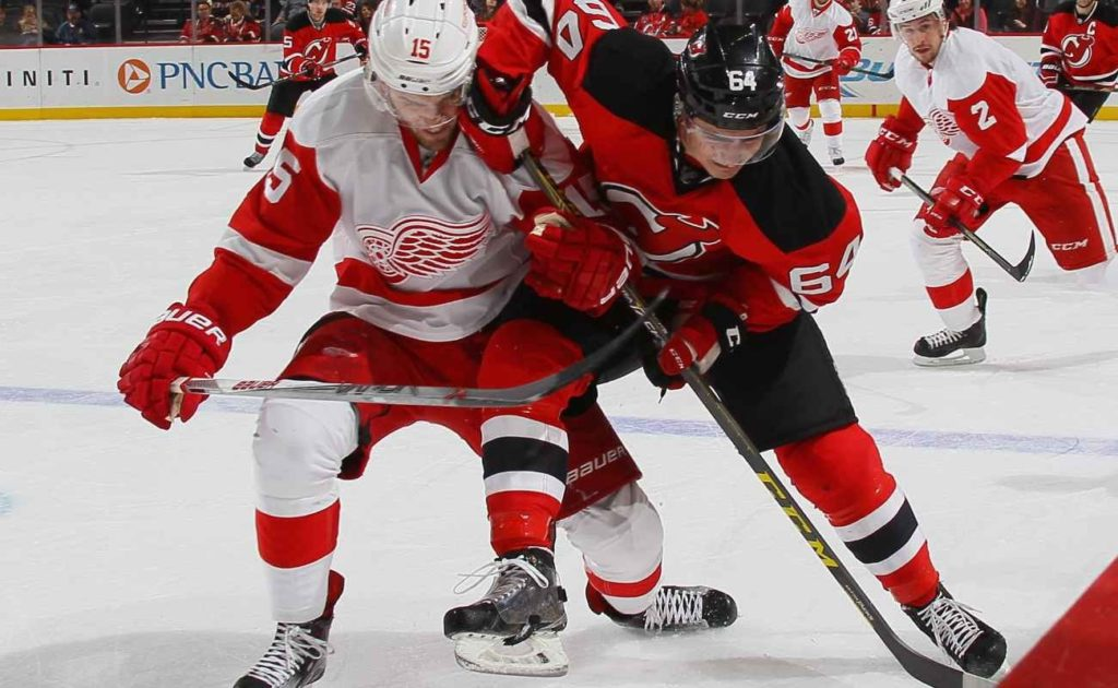 Joe Blandisi #64 of the New Jersey Devils skates in his first NHL game against Riley Sheahan #15 of the Detroit Red Wings