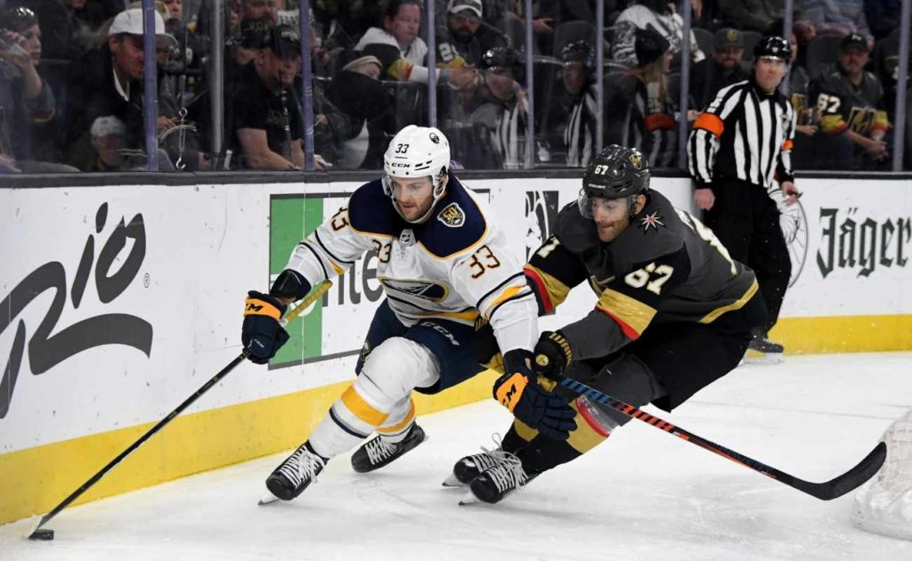 Colin Miller #33 of the Buffalo Sabres skates with the puck against Max Pacioretty #67 of the Vegas Golden Knights