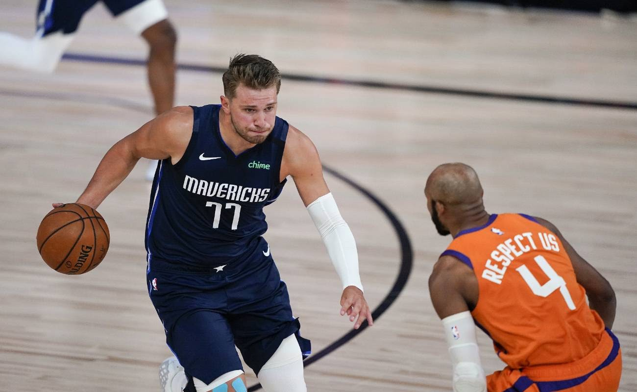 Luka Doncic of Dallas Mavericks drives against Jevon Carter of Phoenix Suns at ESPN Wide World Of Sports Complex in August 2020