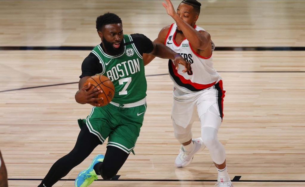 CJ McCollum of Portland Trail Blazers defends against Jaylen Brown of Boston Celtics at ESPN Wide World Of Sports Complex in August 2020