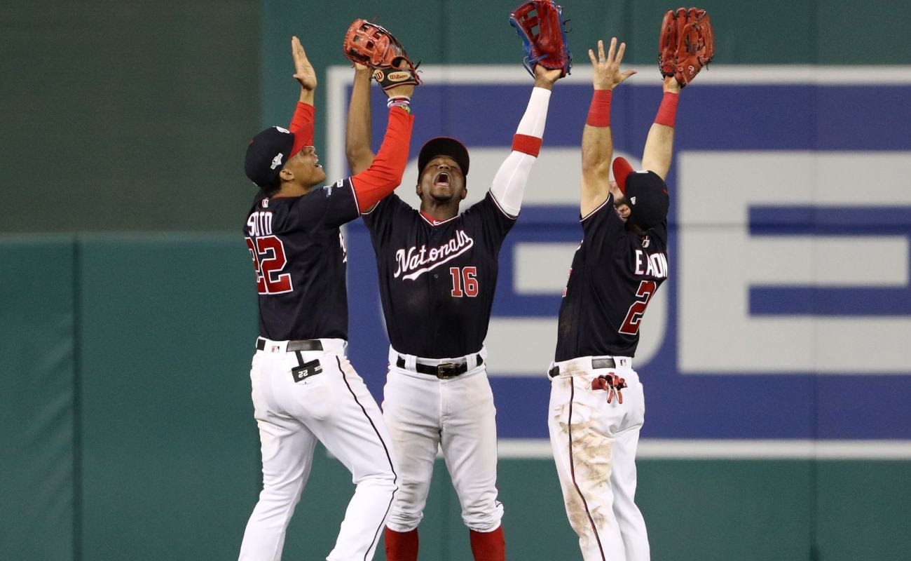 Washington Nationals players Juan Soto, Victor Robles, and Adam Eaton raising arms in the air.