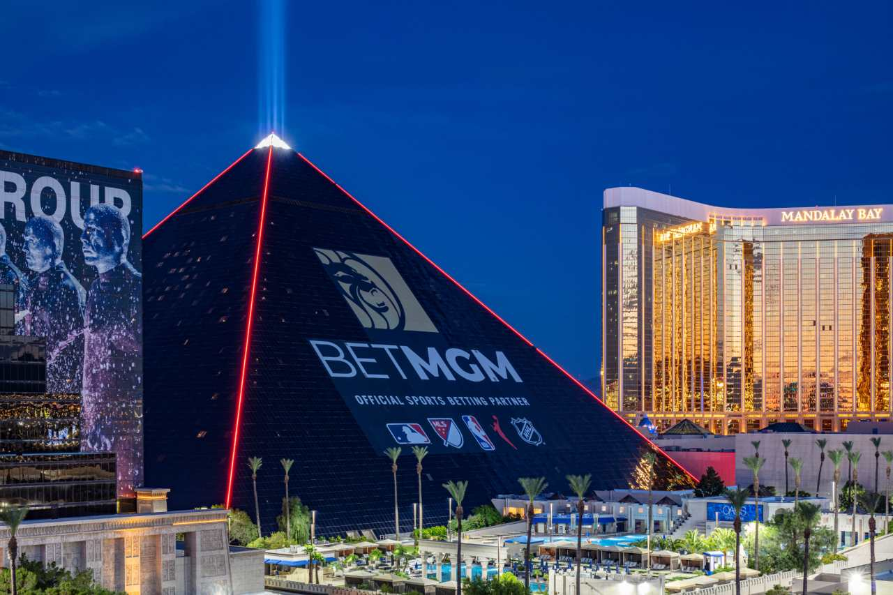 The new BetMGM ad wrap on the Luxor hotel in the evening with red lighting.