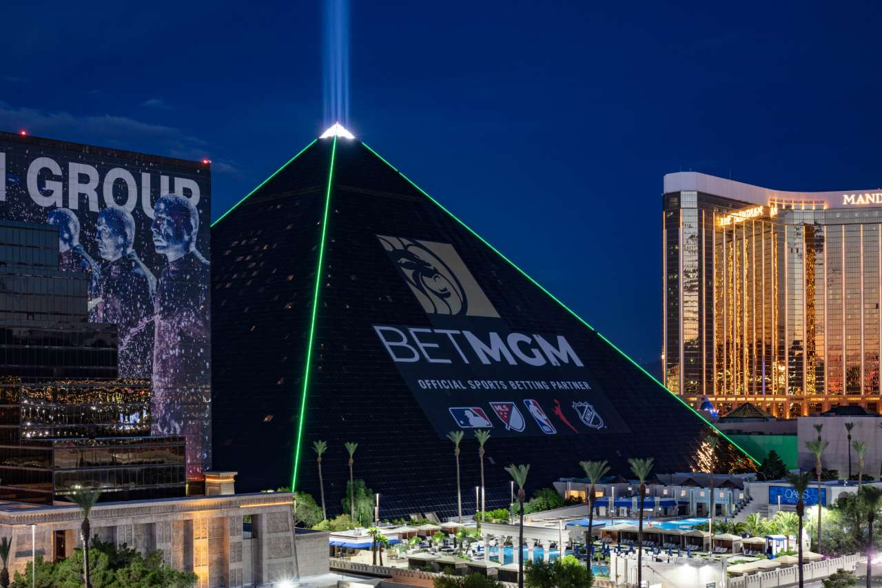 The new BetMGM ad wrap on the Luxor hotel in the evening with green lighting.