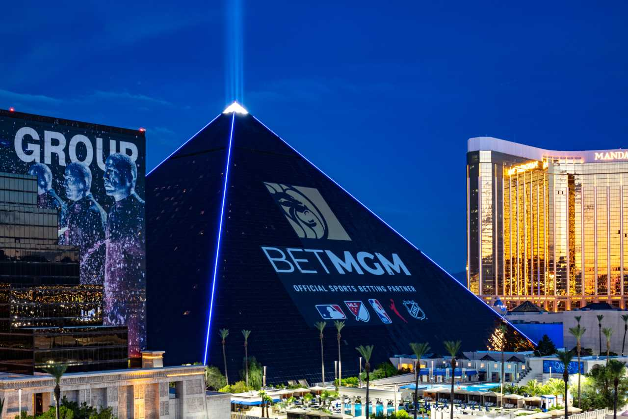 The new BetMGM ad wrap on the Luxor hotel in the evening with blue lighting.
