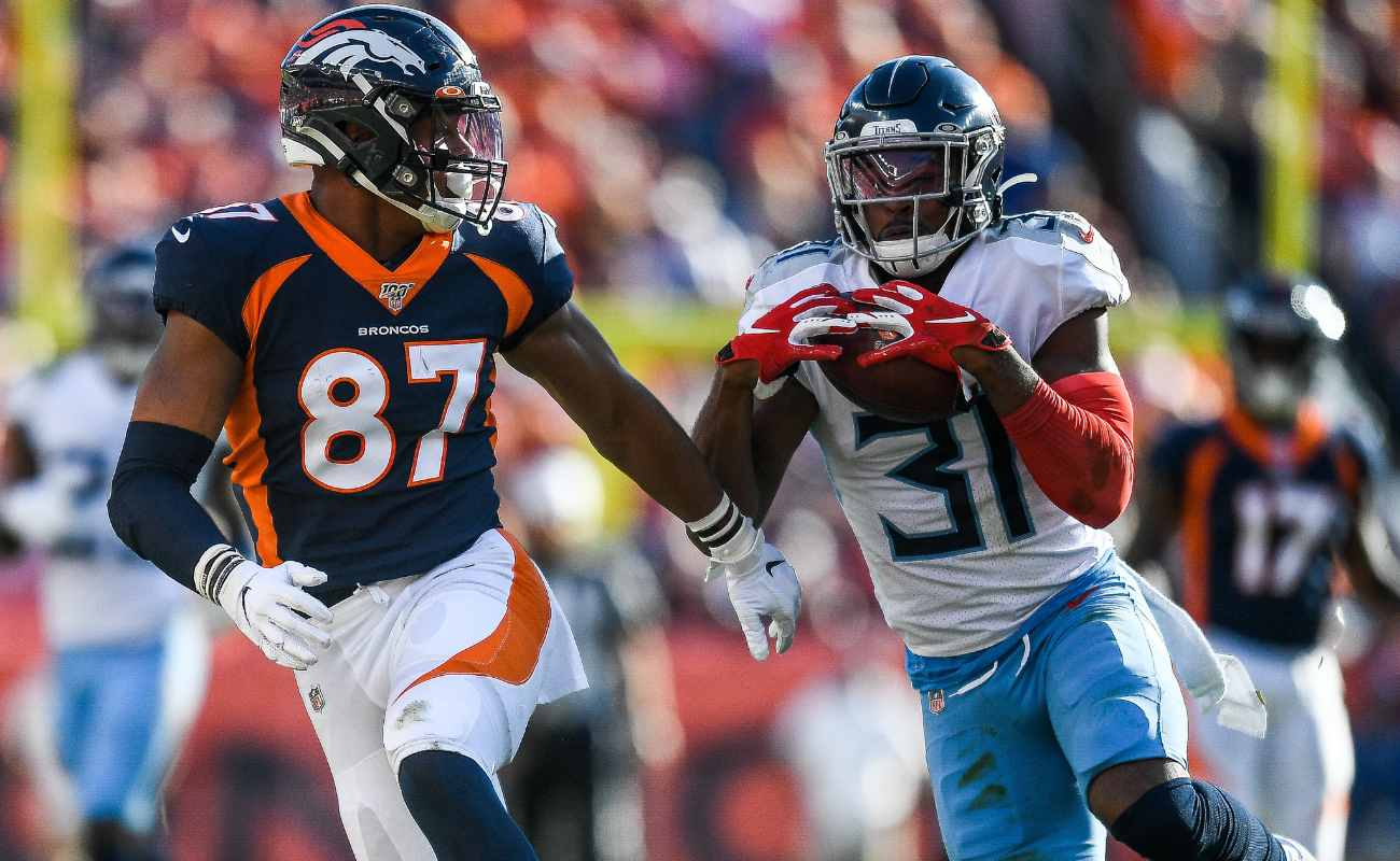 Kevin Byard of Tennessee Titans against Noah Fant of Denver Broncos during game at Empower Field