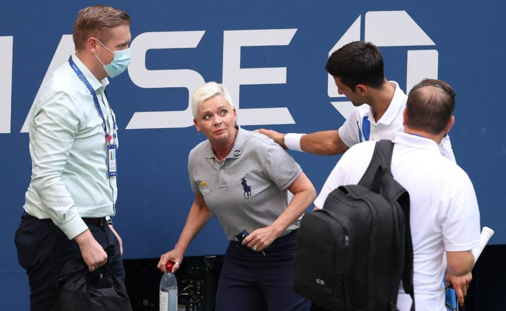 Novak Djokovic tends to lineswoman Laura Clark after inadvertently striking her during his Men's Singles fourth at 2020 US Open