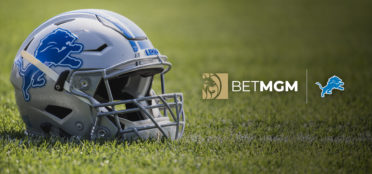 Detroit Lions and BetMGM logos next to a Detroit Lions helmet placed on a field