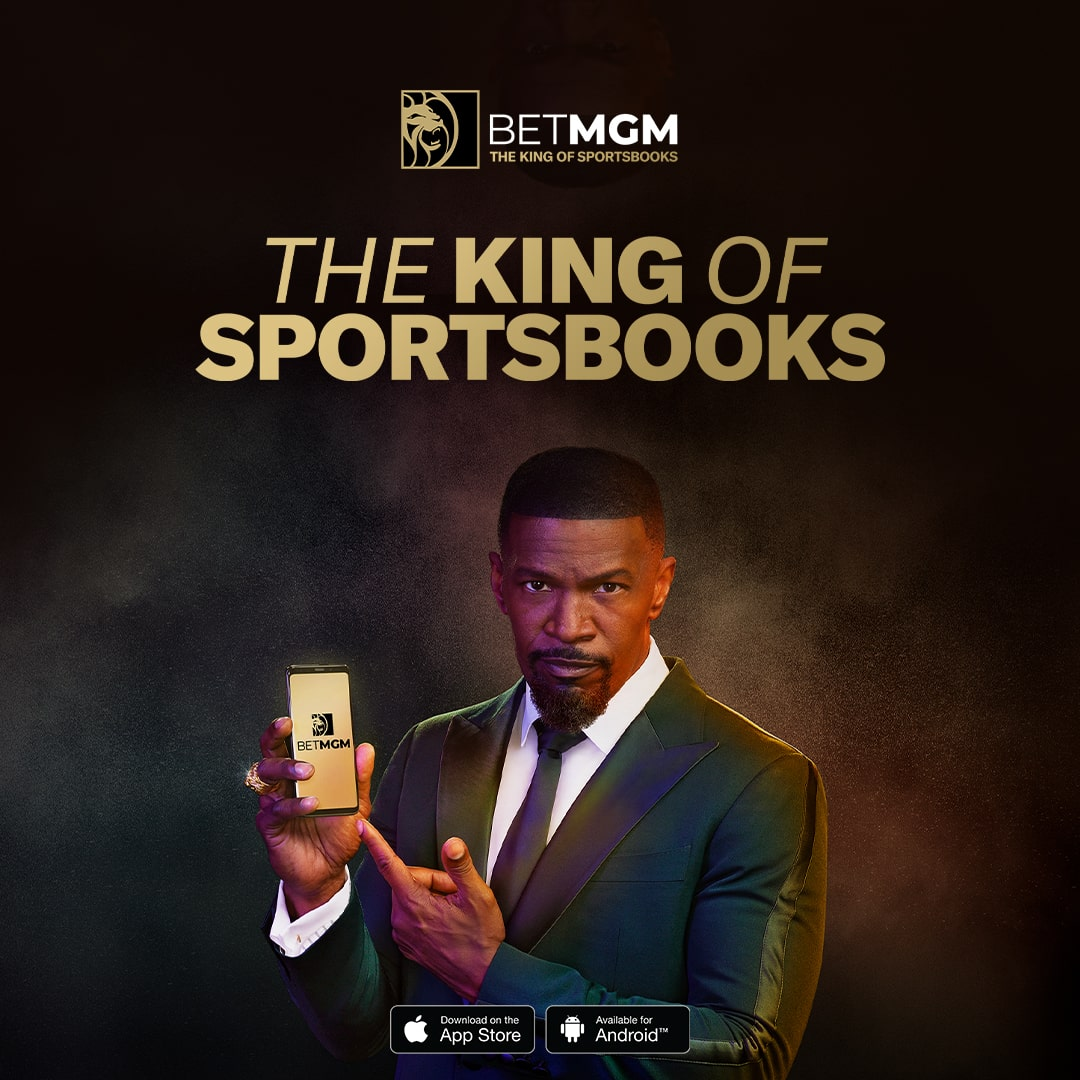 """American portrait of actor and singer Jamie Foxx in a suit, holding a smartphone with a gold BetMGM background for the """"The King of Sportsbooks"""" campaign"""