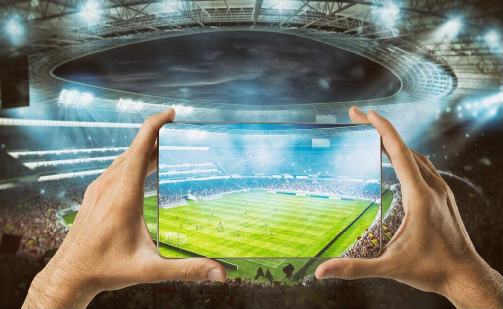 Hands holding a smartscreen mobile at football stadium watching sports live