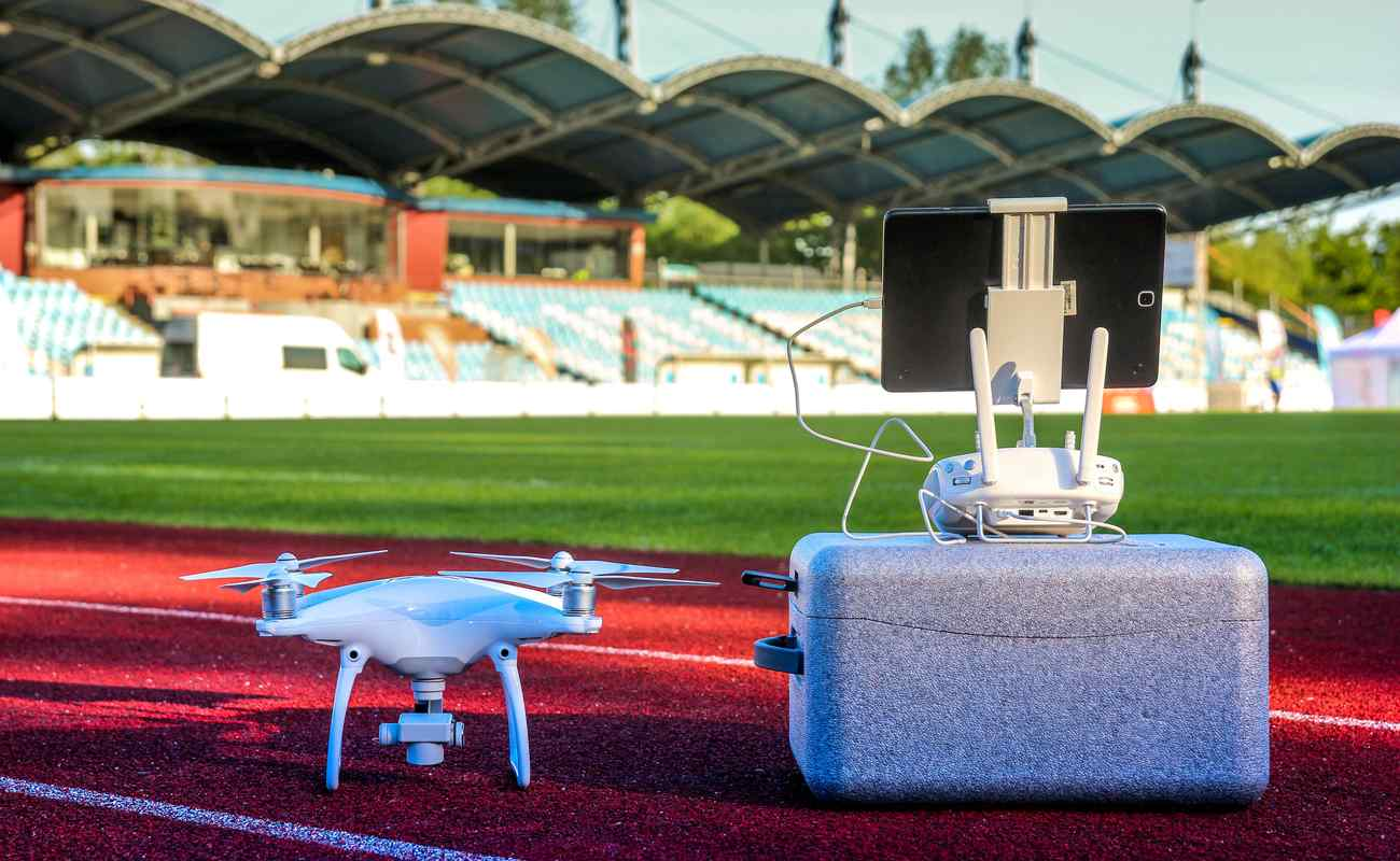 White quadcopter drone with four motors and propellers in large stadium next to carry box and remote controller with touchpad