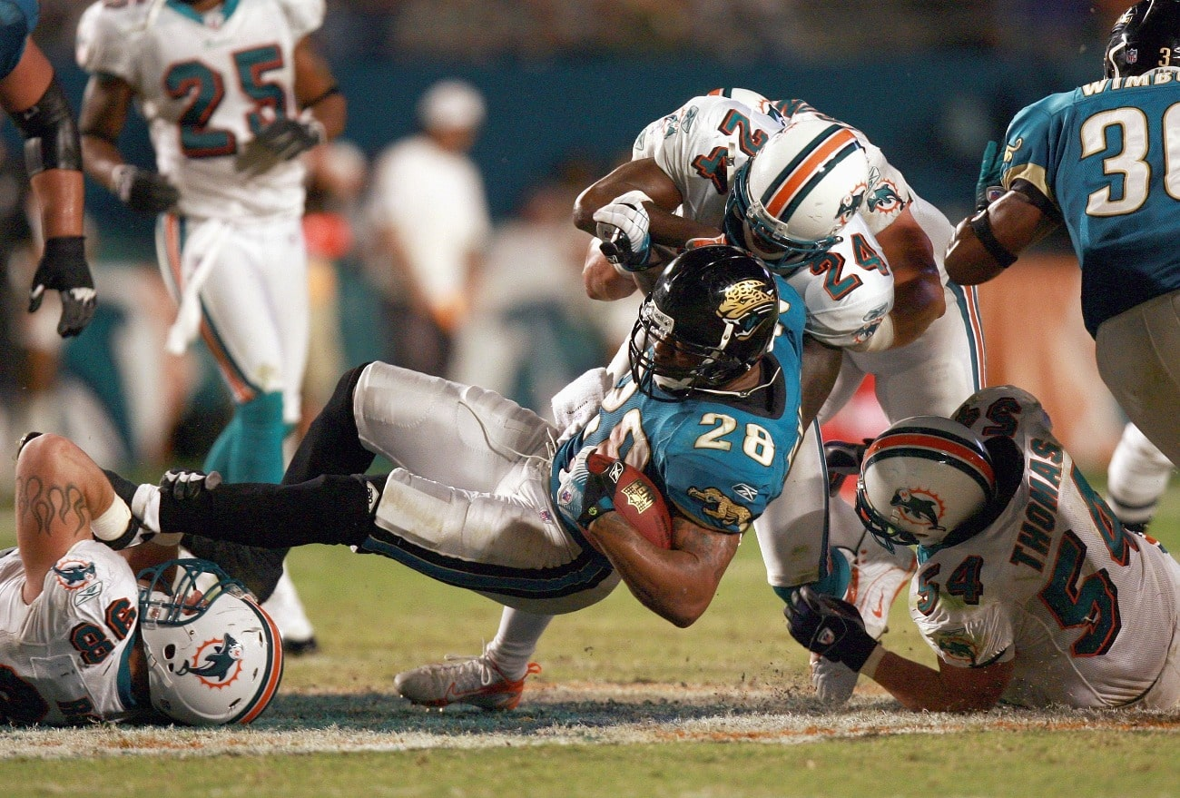 David Richardson #26 of the Jacksonville Jaguars grips the ball as he is tackled by Matt Roth #98 and Renaldo Hill #24 of the Miami Dolphins at Dolphin Stadium on December 3, 2006 in Miami, Florida