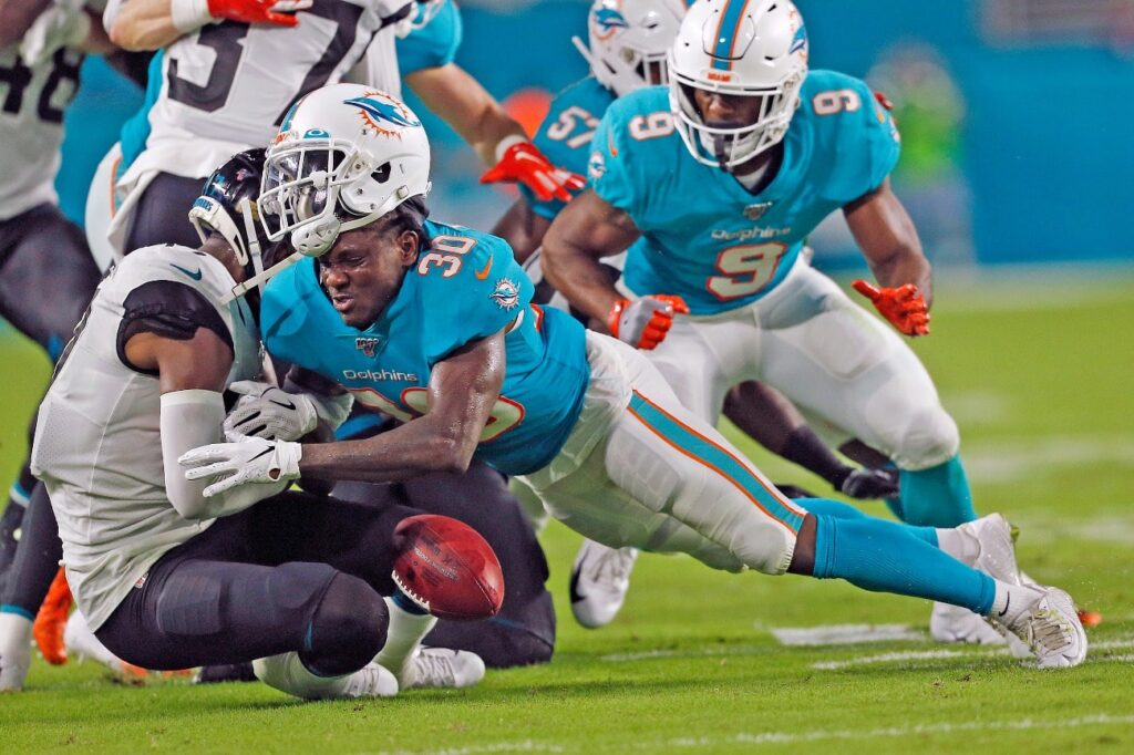 Chris Lammons #30 of the Miami Dolphins has his helmet knocked off as he tackles D.J. Chark #17 of the Jacksonville Jaguars during an NFL preseason game on August 22, 2019 at Hard Rock Stadium in Miami Gardens, Florida