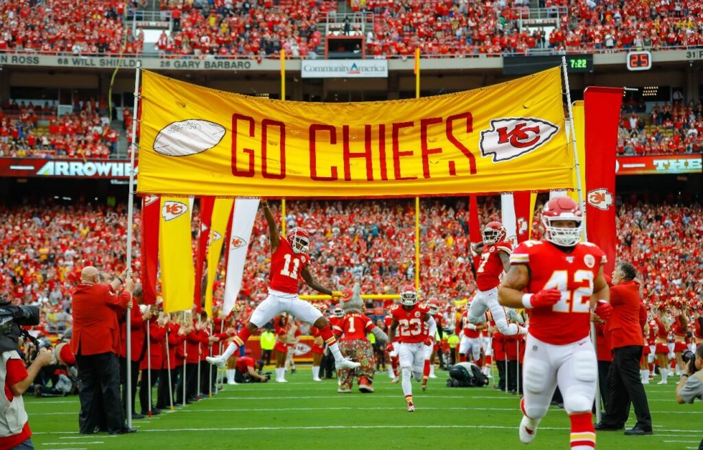 Demarcus Robinson #11 of the Kansas City Chiefs and Mecole Hardman #17 of the Kansas City Chiefs leap to touch the player introduction banner at the start of the game against the Baltimore Ravens at Arrowhead Stadium on September 22, 2019 in Kansas City, Missouri
