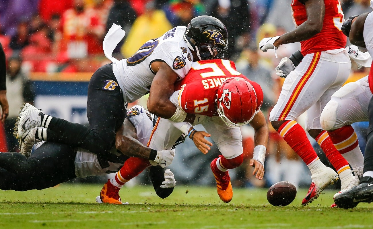 Patrick Mahomes #15 of the Kansas City Chiefs fumbles after being hit by Kenny Young #40 of the Baltimore Ravens on a fourth down play in the third quarter at Arrowhead Stadium on September 22, 2019 in Kansas City, Missouri.