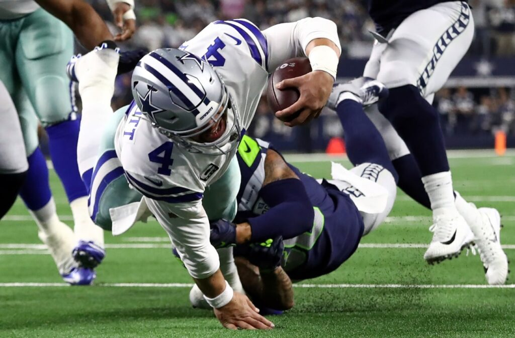 Dak Prescott #4 of the Dallas Cowboys dives to the 1-yard line while tackled by Bradley McDougald #30 of the Seattle Seahawks in the Wild Card Round at AT&T Stadium on January 05, 2019 in Arlington, Texas